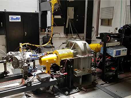 Tesla Model 3 drive unit mounted to a gearbox and dynamometer in a test cell