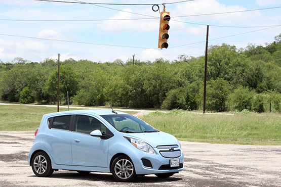 Blue car in a four way stop - EV used for testing.