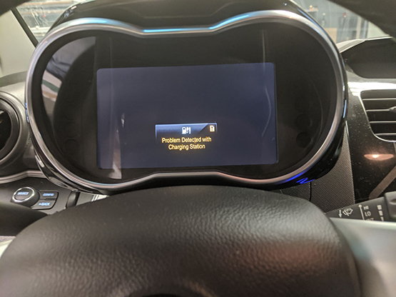 """Car dashboard screen with """"Problem Detected with Charging Station"""" message."""
