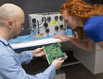 Two engineers in a lab reviewing a green circuit board