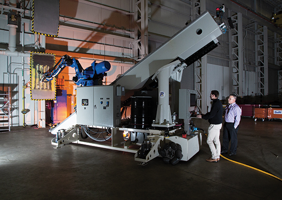 Two engineers standing next to the A5 Robotic System platform