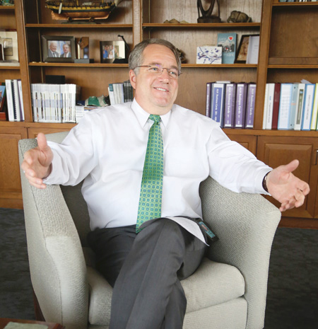 President & CEO Adam Hamilton sitting in an armchair smiling