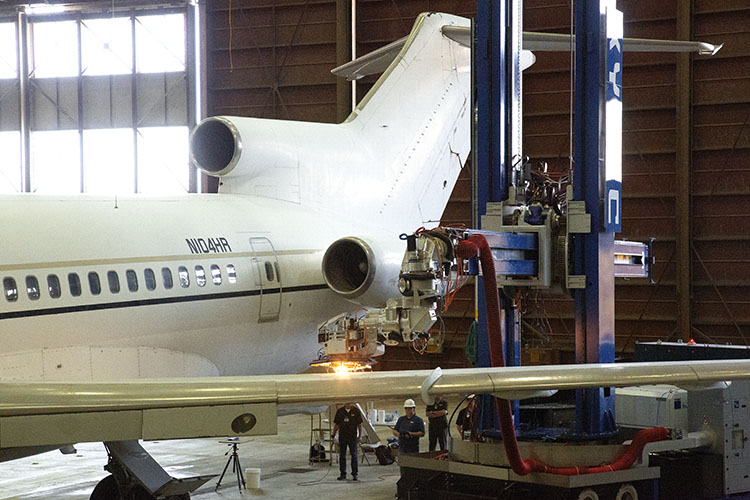 Aircraft in a hangar with a large robot removing paint from the wing with a laser