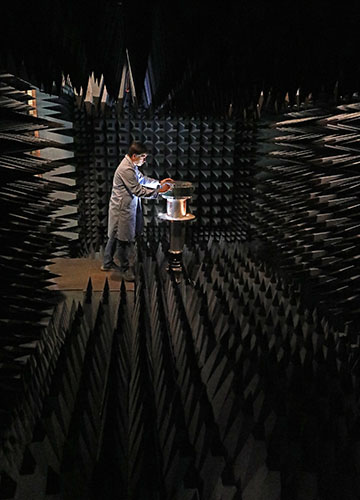 a dark anechoic chamber with a person in a lab coat placing an antenna in the room.