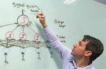 Scientist points to a white board with the process for a neural network scoring a signal quality displayed
