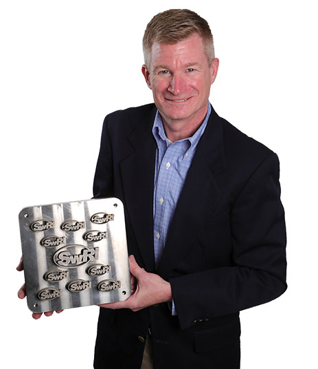 Carl Popelar holding a titanium block with the SwRI logo cut into it numerous times