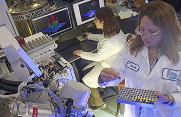 Two scientists in white coats inside a biology lab with equipment