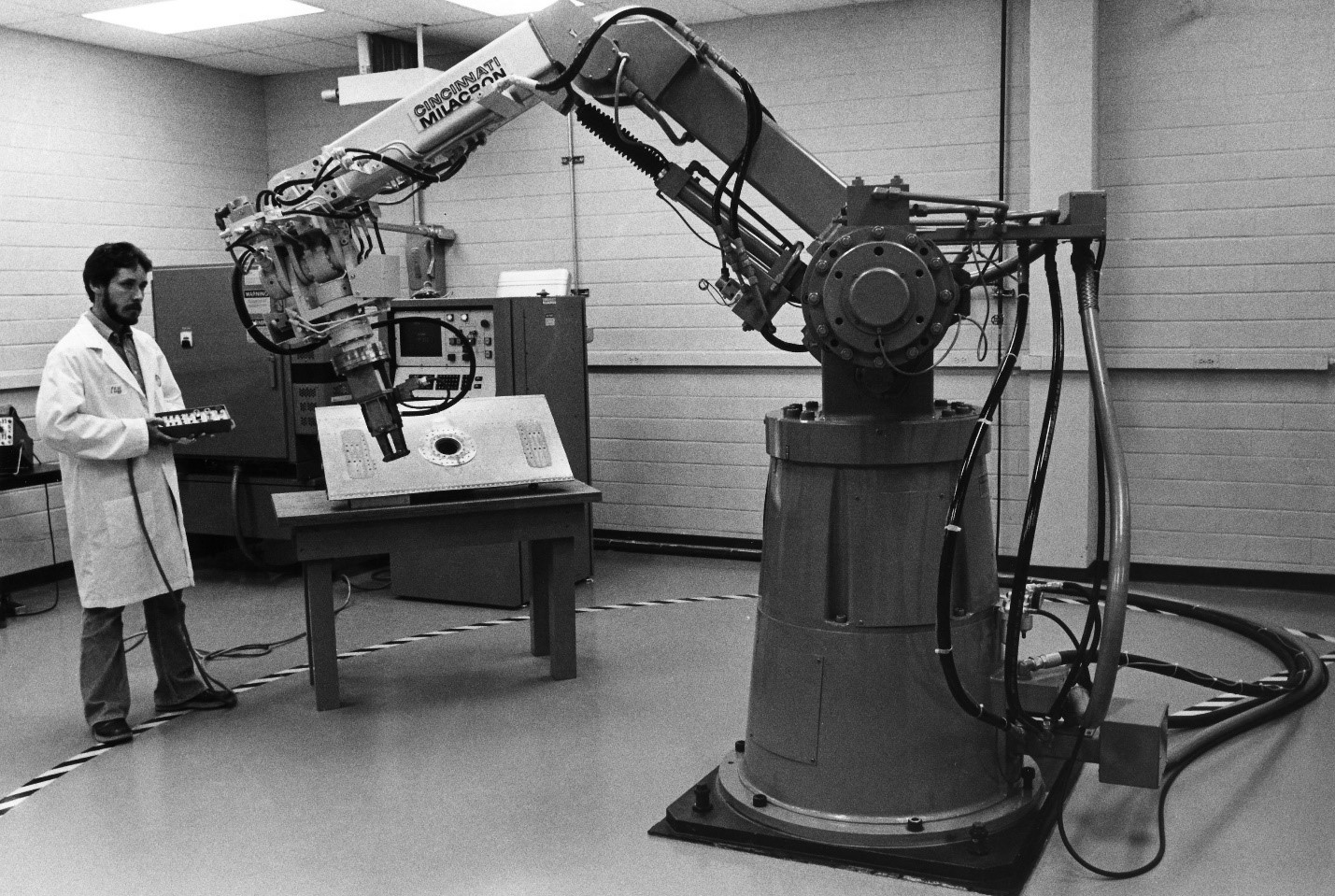 Black & white photo showing a man in a lab coat standing near a large robotic arm