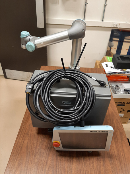 cobot with industrial arm and controller sitting on table