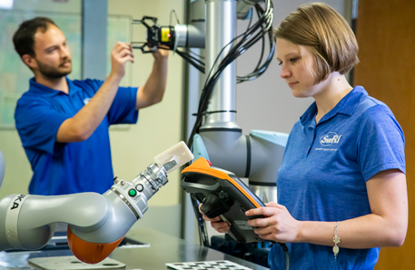 woman holding a cobot teach pendant in front of a cobot with a man in the background working on another robot