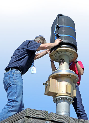 Two people adjusting an upright antenna