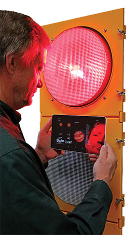 Yellow traffic signal with a person holding a tablet with traffic warnings