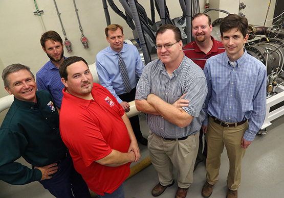 Seven men standing in front of high-inlet-temperature combustion system