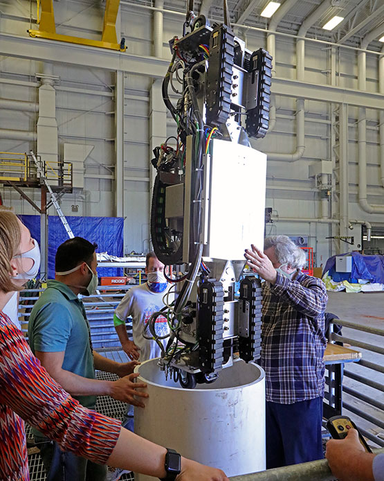 team members place a mobile robot into a tight cylinder