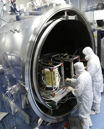 Two people in clean suits placing CYGNSS into a testing chamber