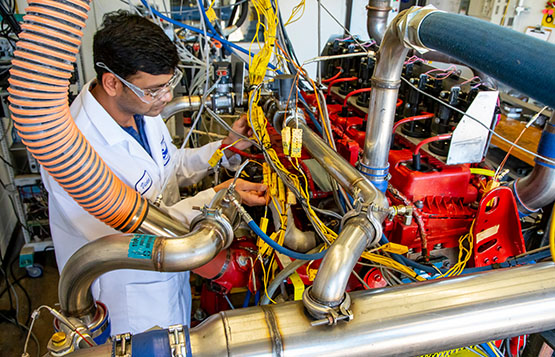 Engineer monitoring a D-EGR engine colored red with wires running from the engine to various sensors