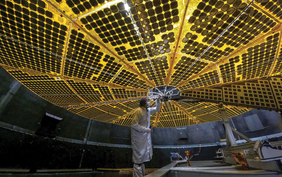 Engineer deploying one of Lucy spacecraft's massive solar arrays in a thermal vacuum chamber
