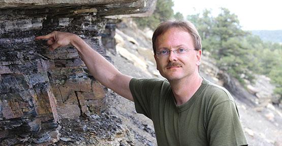 Dan Durda pointing towards a rock cliff