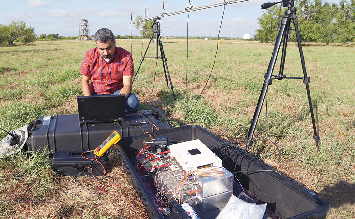 Maher Dayeh kneeling in grassy field working on a laptop sitting on top of equipment cases