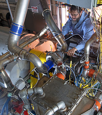 Technician monitoring a large diesel engine test stand