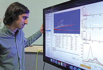 A scientist reviews data on a large monitor in front of him.