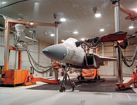 Large mobile orange robot working on an aircraft in a lab