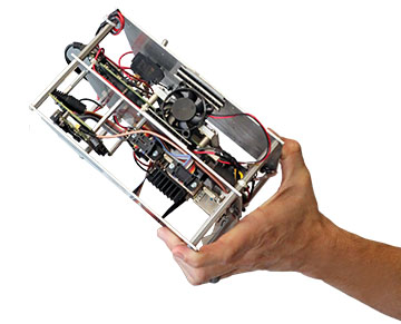 Hand holding a metal frame with electronic components inside