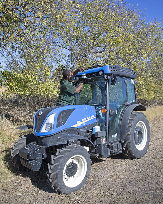 A large blue tractor with a person adjusting a sensor on the roof