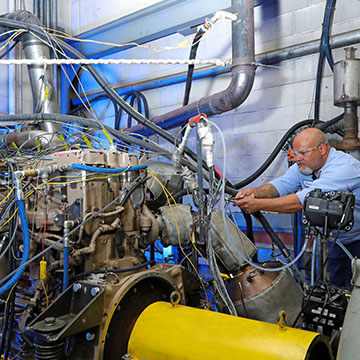 technician working on a heavy-duty engine in a laboratory