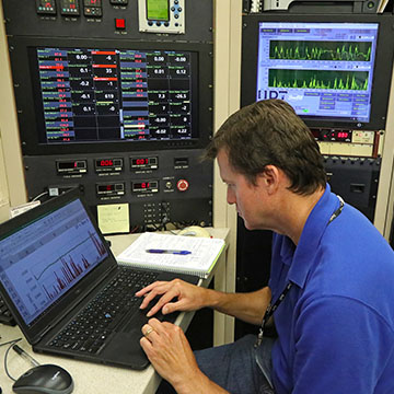 Analyst monitoring graphs of data on three screens