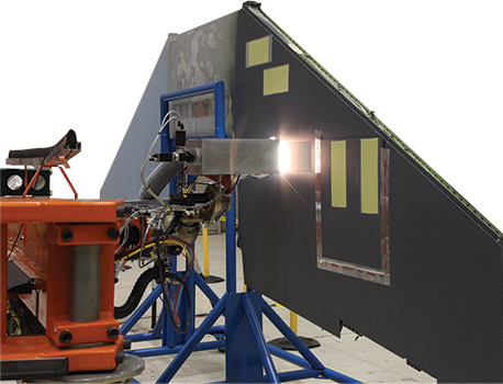 A robot with a high precision laser removing paint on a wall