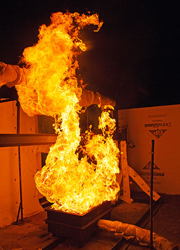 Fire test of an I-beam with yellow flames shooting into the air