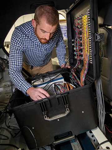 Senior Research Engineer Kevin Jones using a mobile data acquisition system inside of an electric vehicle.