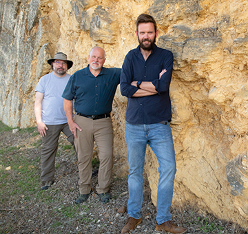 Dr. Kevin Smart, Dr. David Ferrill and Dr. Adam Cawood standing in front of a rock structure.