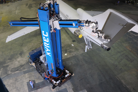 Blue robot comprised of two segments - the first is vertical with XYREC in white lettering; the second is horizontal to the ground with a laser attached. The robot is using a laser to remove an aircraft coating