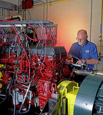 Technician standing behind a large red automotive test cell