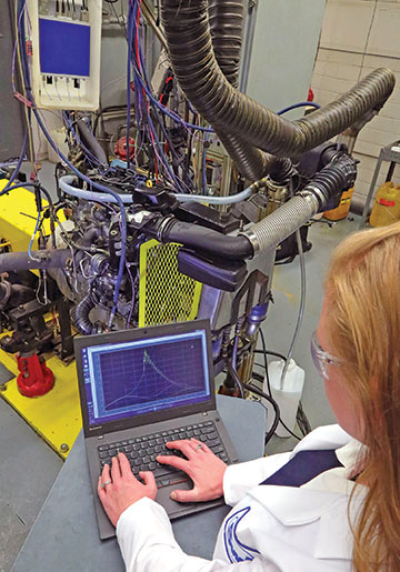 A lubricant testing lab with an engine on a test stand a female engineer reviewing data on a laptop