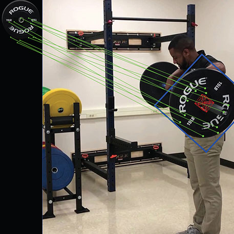 A person lifting a barbell with the software tracking the motion of the barbell plate
