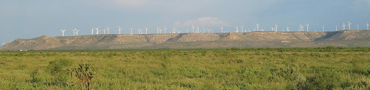 Panoramic of a mesa in the distance with many windmills on top.