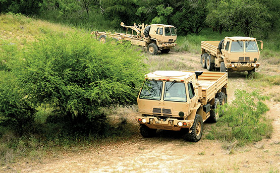 Military heavy truck convoy on a dirt road