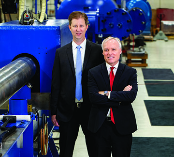 Dr. Nicholas Mueschke (left) and Dr. James Walker standing in front of blue machinery