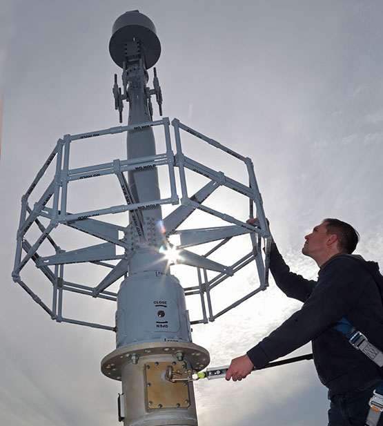 Mast antenna in the air with a technician working beside it