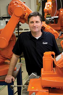 Portrait of Paul Evans standing among several orange robots