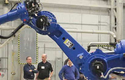 a large blue robotic arm in a warehouse