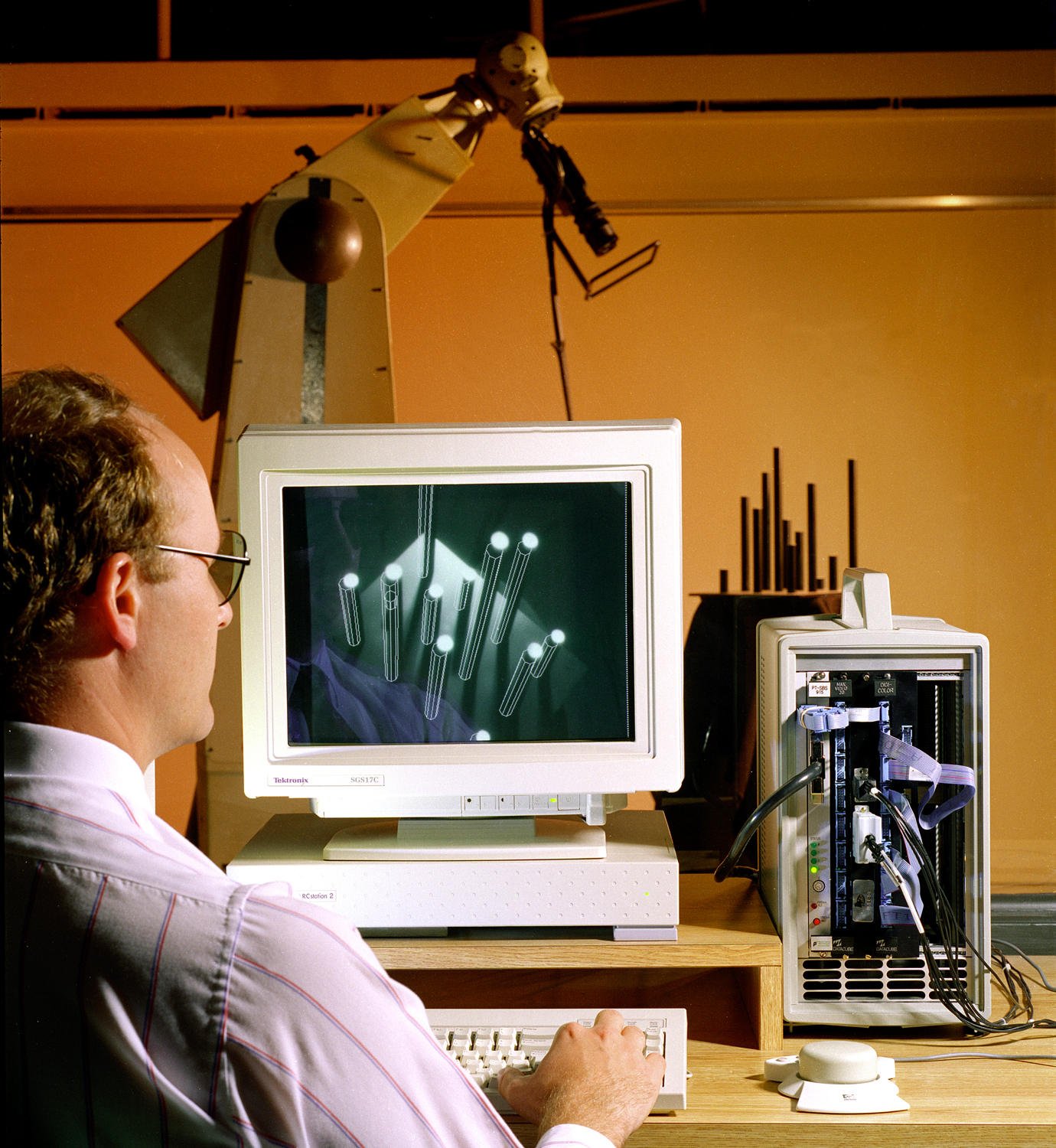 Man sitting in front of computer with robotic arm reaching down