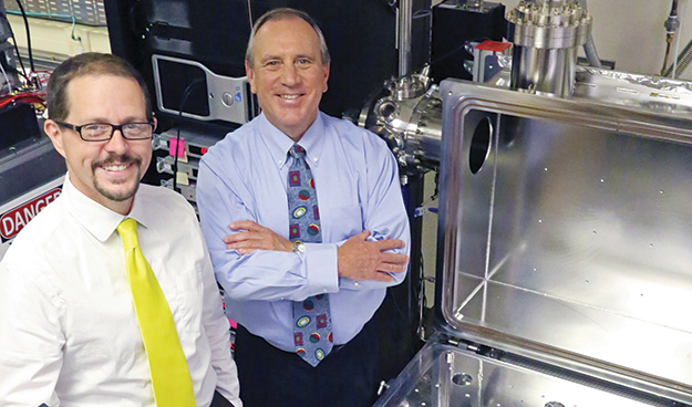 Dr. Kurt Retherford (left) and Dr. J. Hunter Waite standing side-by-side inside a laboratory