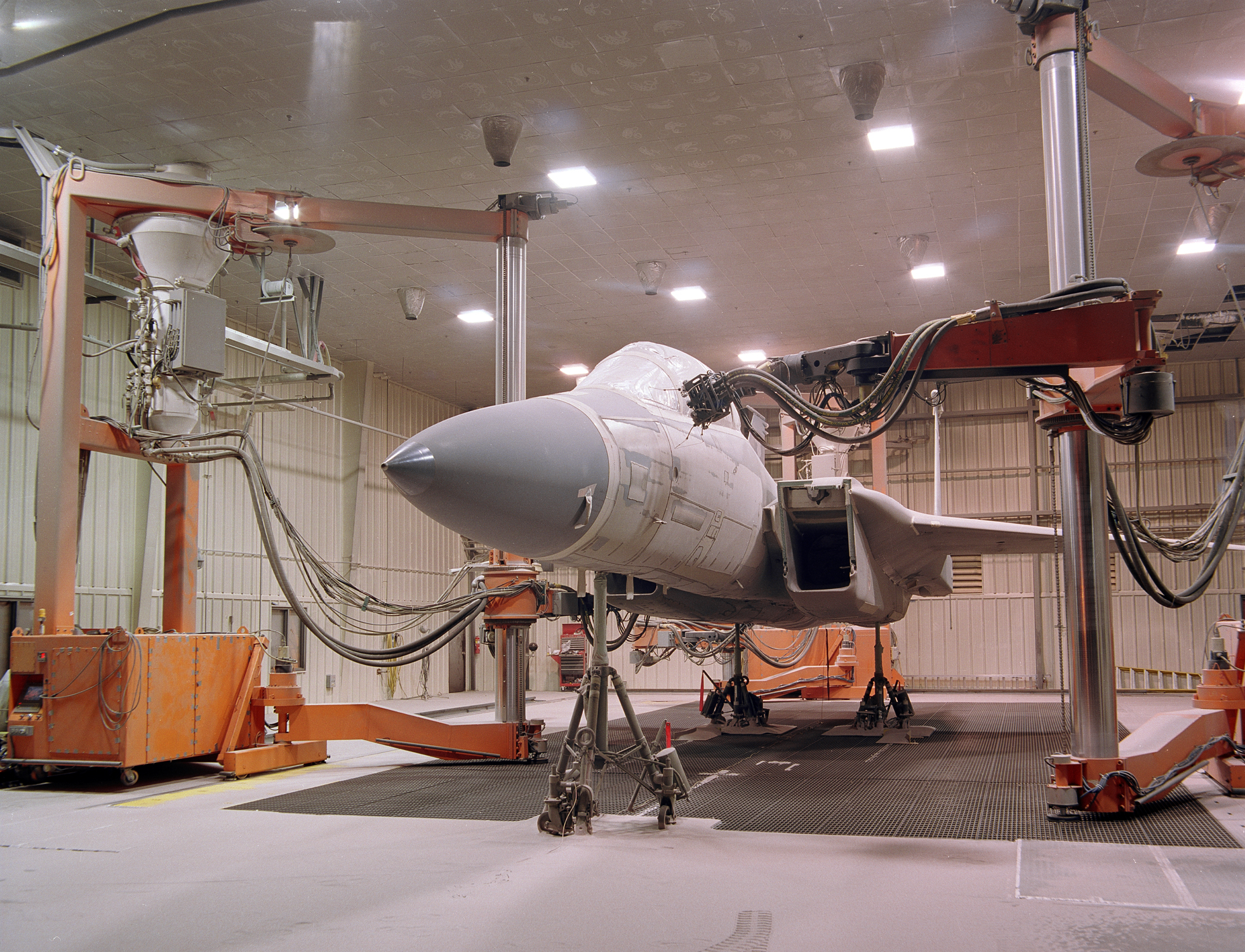 Large orange robots removing coatings from an F-15 aircraft