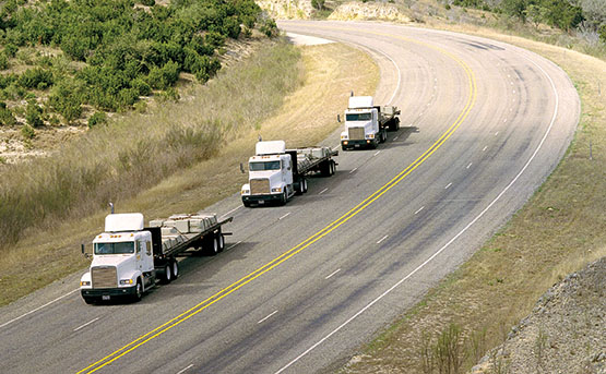Semi-truck convoy on a hilly road