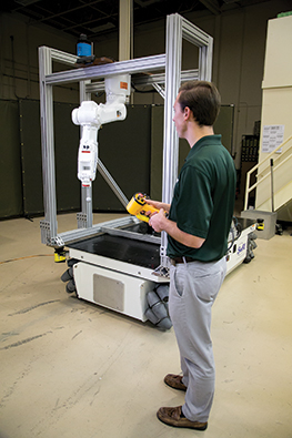 Engineer using a small-scale mobile manipulator system in a lab