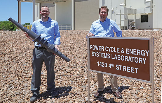 Aaron McClung holding a turbine shaft and Tim Allison standing behind a brown building sign
